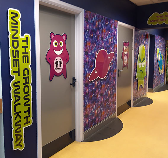 Spaced themed and Dojo wall signs in a primary school corridor